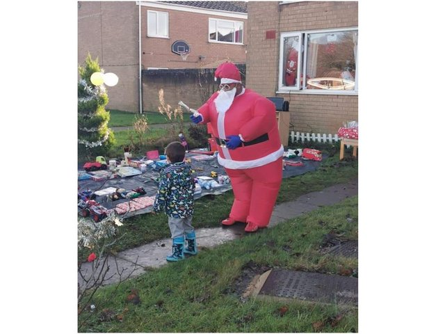 Matthew Hextall collects a present from Prabhu Natarajan, who dressed as Santa to help raise the Christmas spirit in his Bretch Hill, Banbury neighbourhood