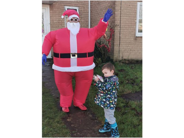 Matthew Hextall collects a present from Santa, Prabhu Natarajan, in the Bretch Hill neighbourhood of Banbury