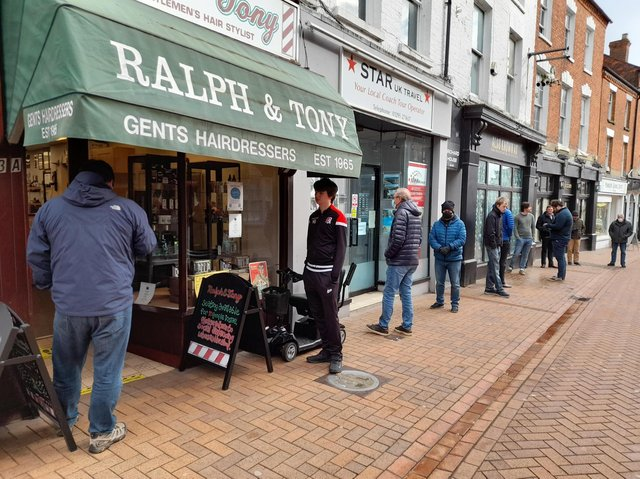 More than a dozen people wait for a haircut outside Ralph & Tony barbers in Parsons Street