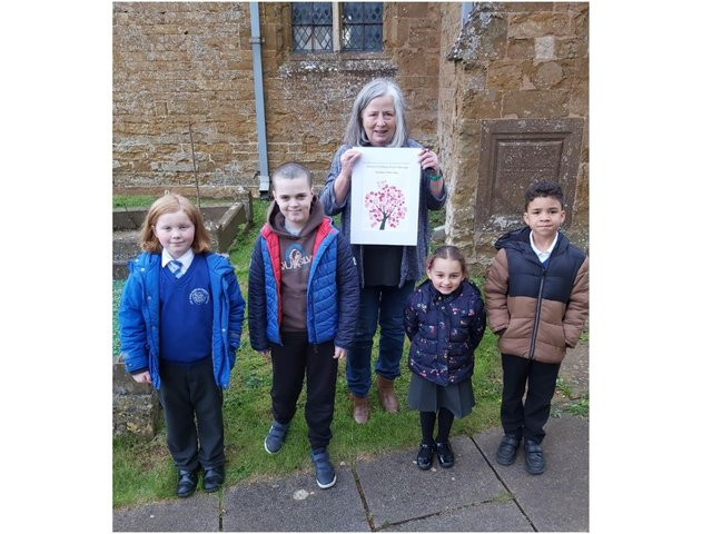 Wroxton Primary School pupils: Riley Powell, Aidan Parker, Ioana Let and Blake Mukombe, pictured with Reverend Alicia holding her picture of a Cherry Blossom tree, which every child in school contributed to. (Image from Wroxton Primary School)