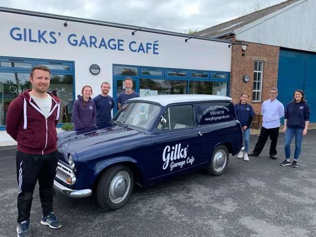 The Gilks' Garage Cafe staff and Cameron Mair from C.M. Signs stand around the cafe's new delivery van affectionately known as 'Cobby' - officially a 1961 Commer Cob.