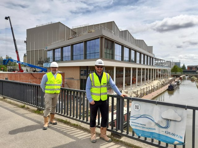 Chris Hipkiss, with Cherwell District Council, and Ben Parker with McLaren construction company stand on a bridge over the canal at the Castle Quay waterfront development