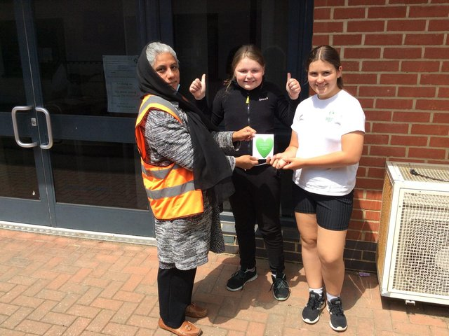 Nadra Masood (a lunchtime supervisor) receiving her thank you heart message from Isobel White and Julie Rutowska in year six at Dashwood Academy Banbury as part of Thanks a Teacher Day